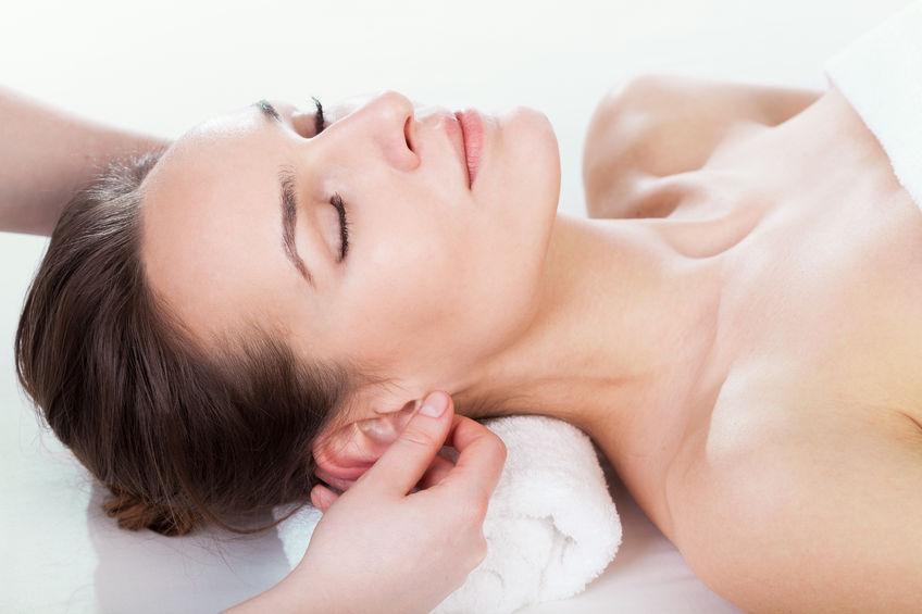 27245272 - woman enjoying ear massage at beauty salon
